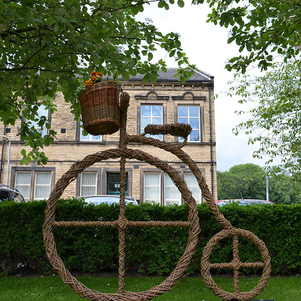 Willow weave penny farthing bike sculpture with bike basket full of planted flowers